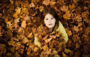 Девочка в осенних листьях.